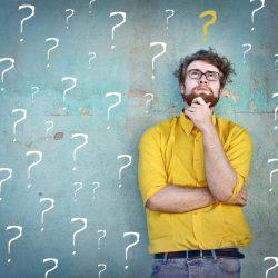 Ein Mann mit gelben Shirt vor einer Betonwand mit Fragezeichen.