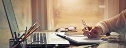 Mann sitzt am Schreibtisch vor einem Laptop und macht sich Notizen