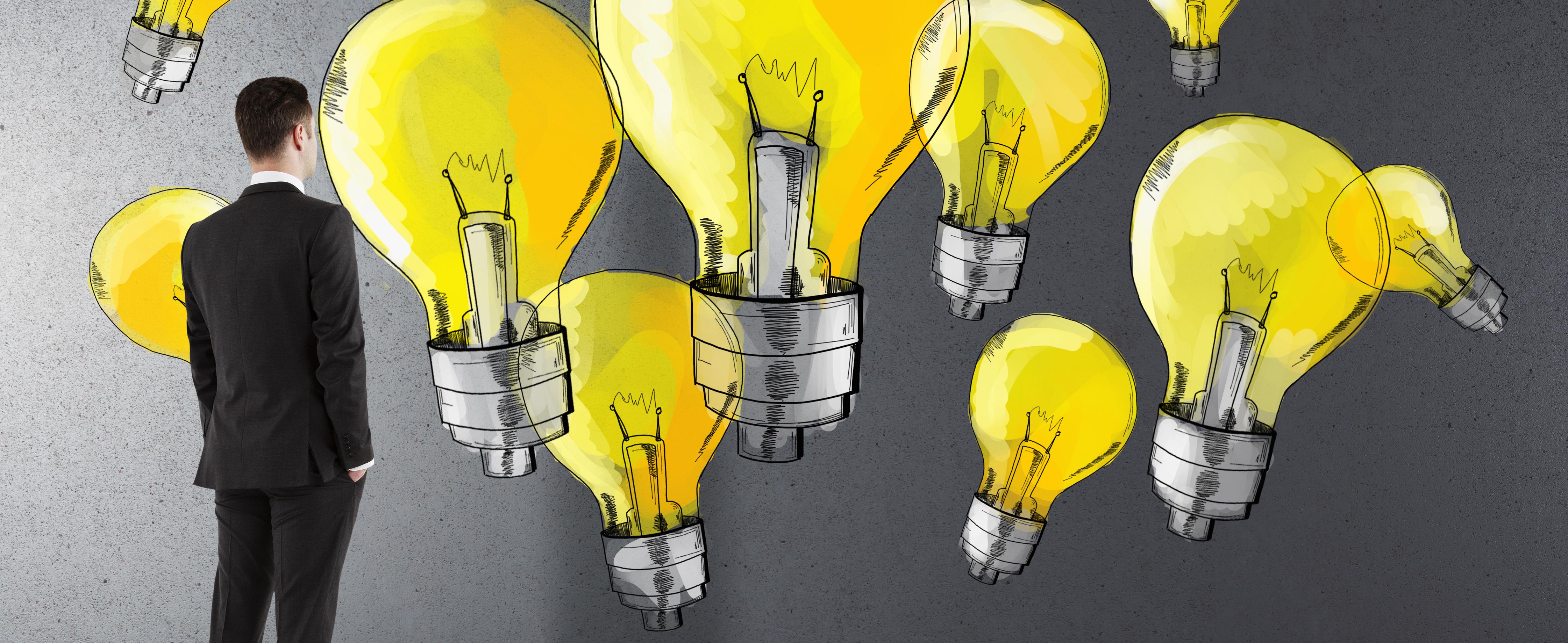 Mann im Anzug steht vor einer Wand mit gelben Glühbirnen - Führungskompetenz