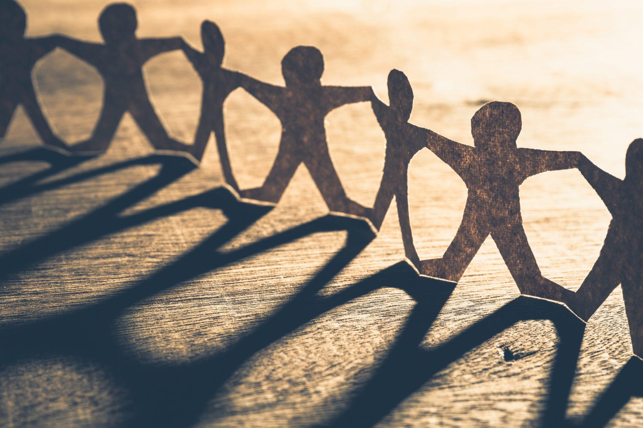 Symbolfoto für Kooperation: Eine Papierkette aus Menschen steht auf einem Tisch