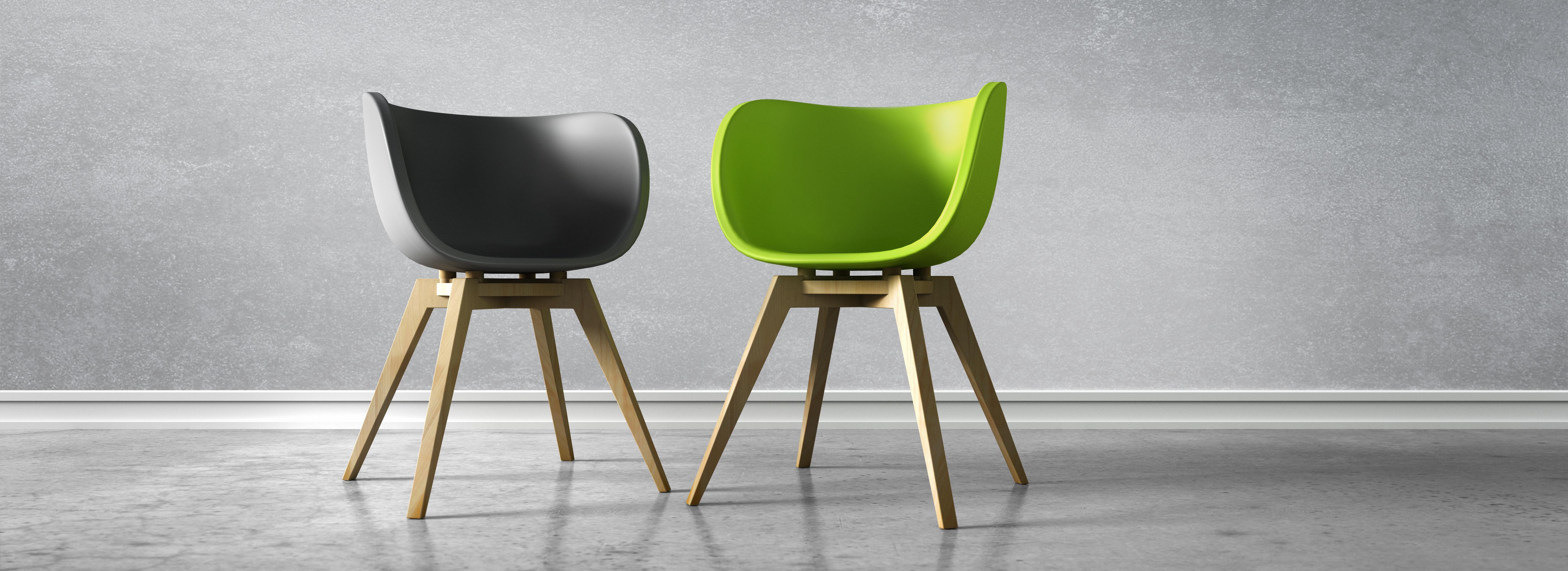 Ein schwarzer und ein grüner Stuhl stehen vor einer Betonwand