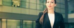 Eine Berufsanfängerin im Business Outfit blickt selbstbewusst in die Kamera