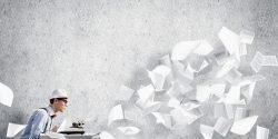 Symbolfoto Ein junger Autor sitzt vor einer Schreibmaschine, beschrieben Blätter fliegen von ihm weg.