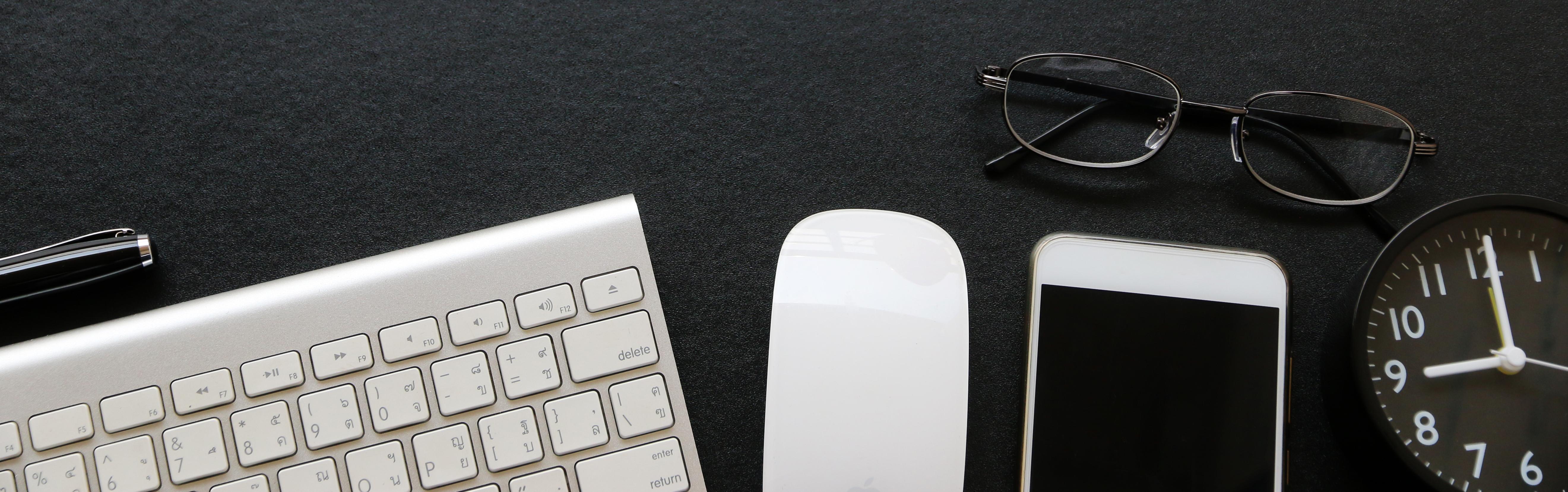 Tastatur, Maus, Smartphine, Uhr und Lesebrille liegen auf einem schwarzen Schreibtisch