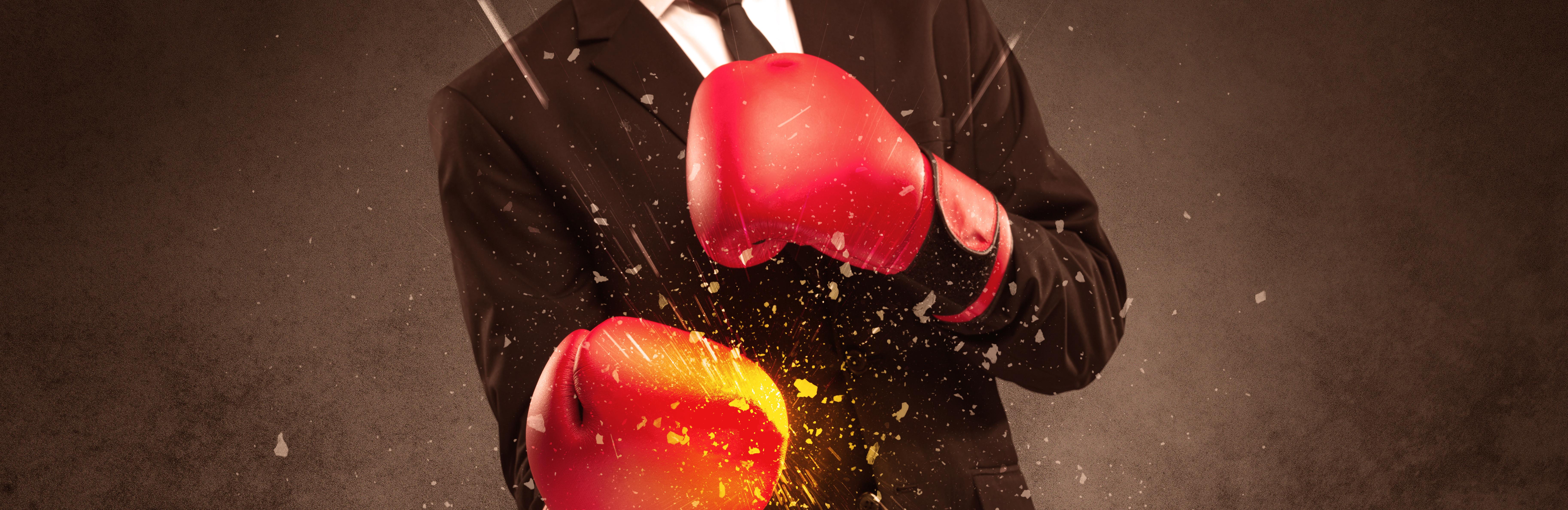 Symbolbild Mann im Anzug trägt Boxhandschuhe