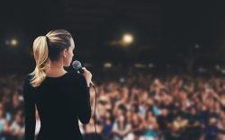 Frau mit Mikrofon vor Publikum, Thema Rhetorik