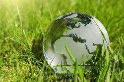 Eine Glasweltkugel liegt im Gras - Nachhaltige Entwicklung