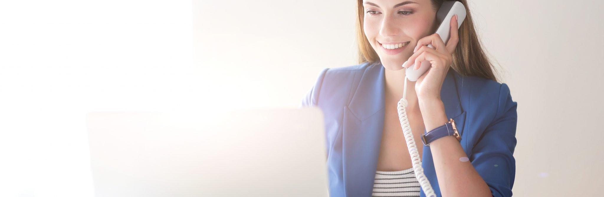 Eine junge Frau sitzt vor ihrem Laptop und hat den Telefonhörer in der Hand