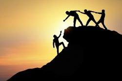 Menschen helfen sich auf einen Berg - das Wir-Gefühl