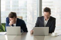 Männer vor Laptops lachen