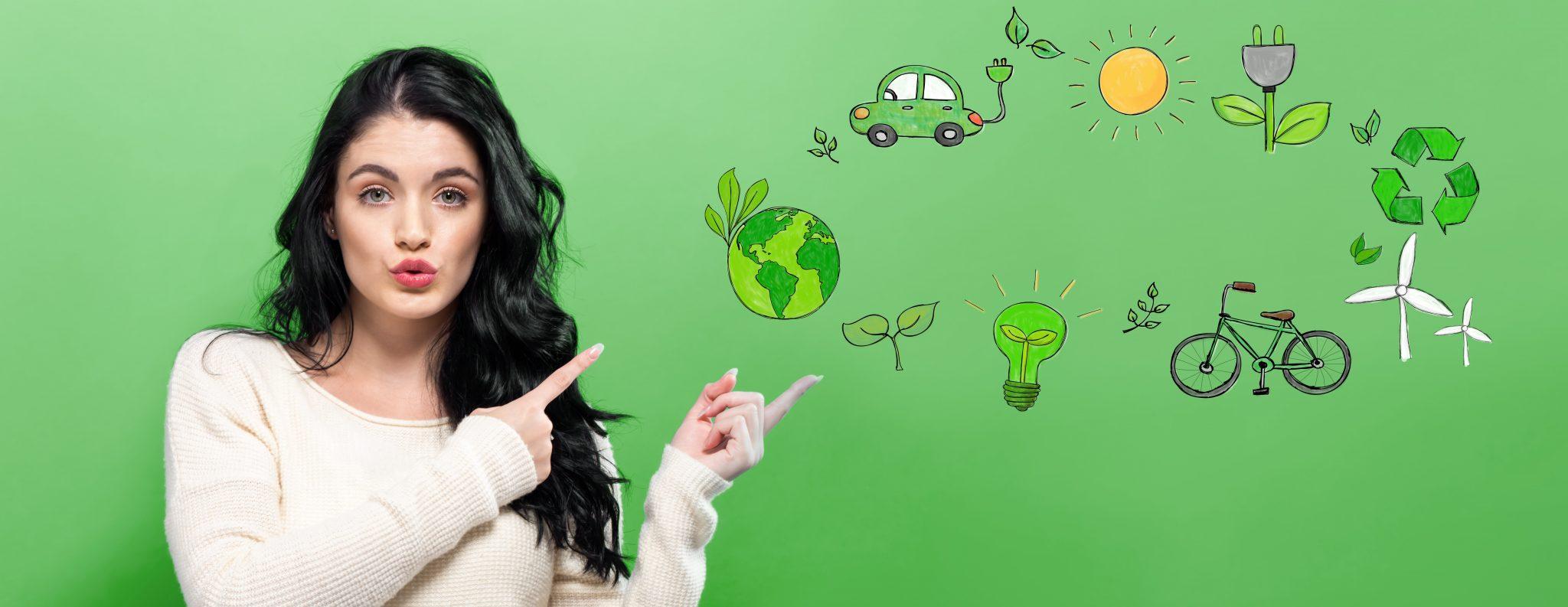 Frau die mit ihren Fingern auf eine grüne Welt, ein grünes Fahrrad, auf Windräder und auf eine Sonne zeigt