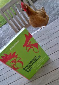 Ein Huhn sitzt auf einem Stuhl vor einem metropolitan Buch