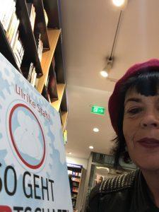 Eine Frau mit Hut hält das Boch So geht WIRtschaft in einer Buchhandlung hoch