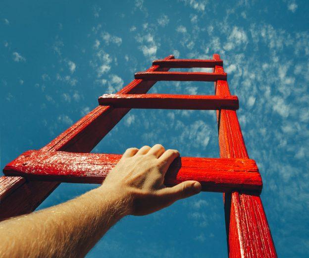 Symbolfoto: eine rote Karriereleiter ragt in den Himmel