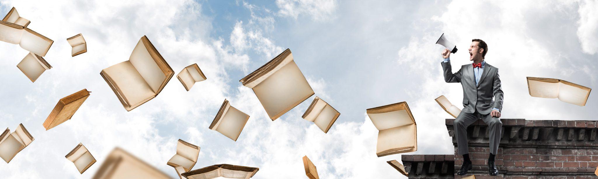 Mann sitzt mit Lautsprecher auf Dach mit fliegenden Büchern