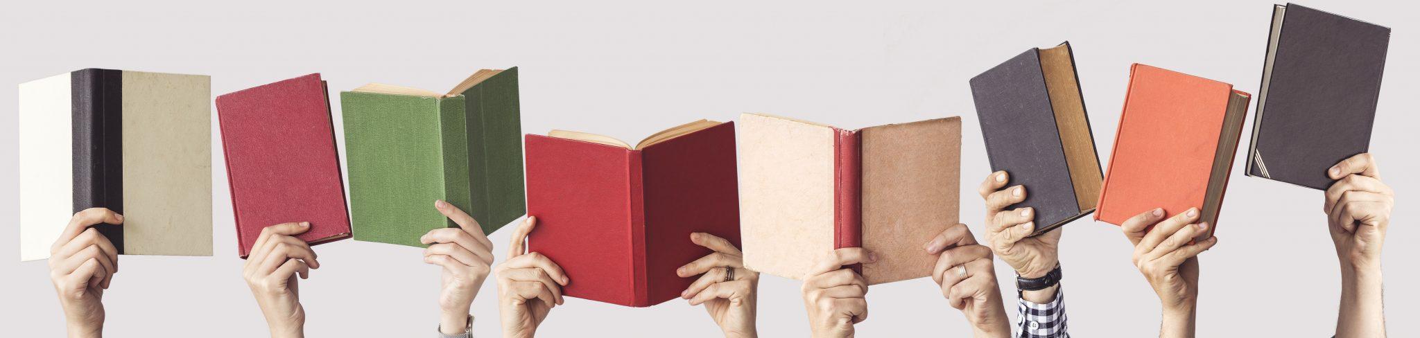 Mehrere Personen halten bunte Bücher hoch