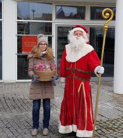 Melaime und Oliver verteilen Schokolade als Nikolaus