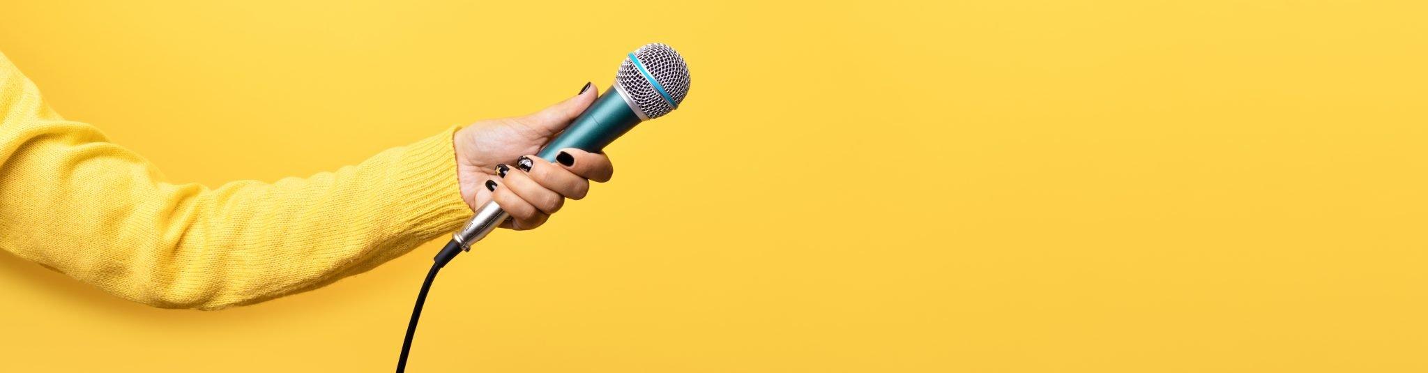Hand mit Mikrofon vor gelber Wand