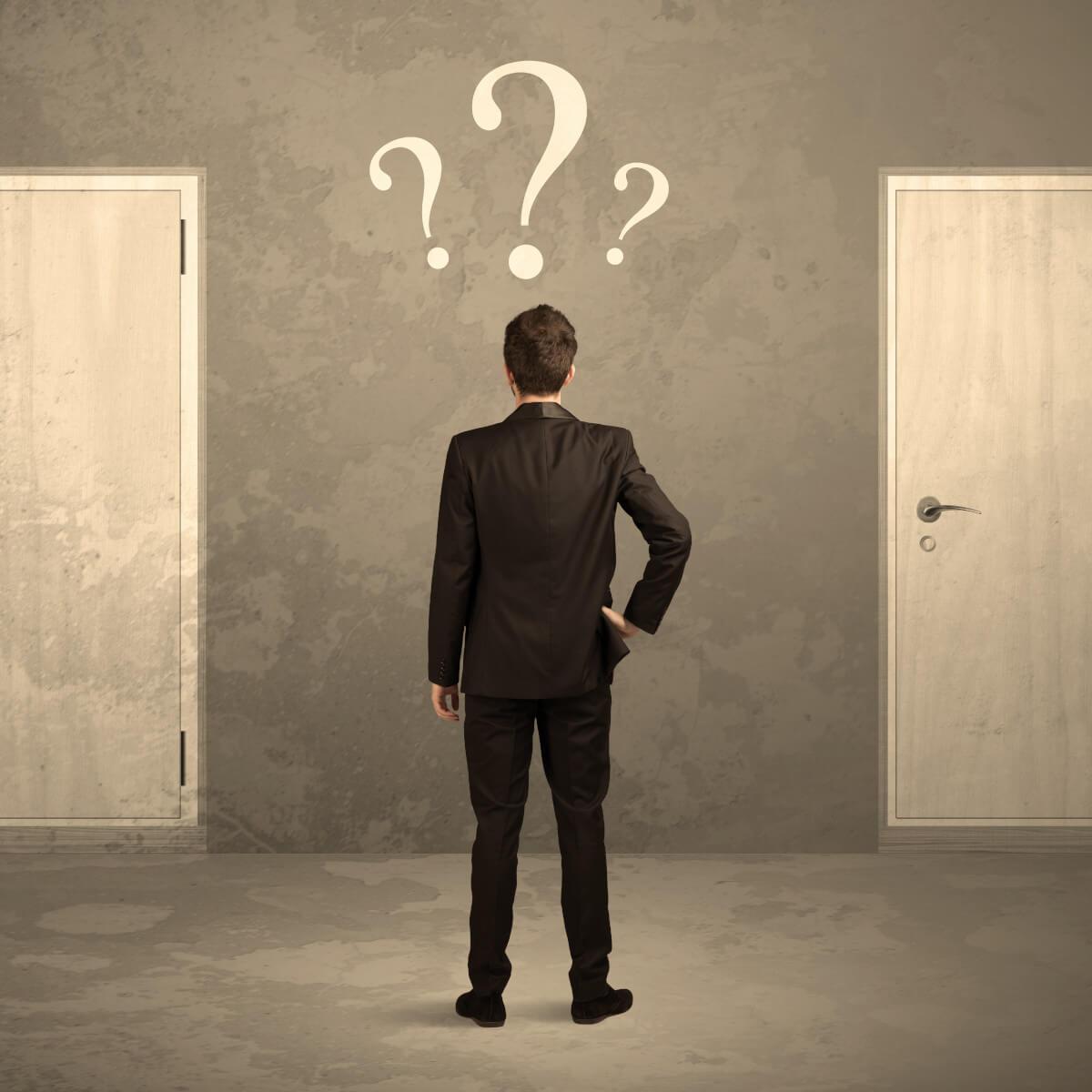 Mann im Anzug vor zwei Türen Entscheidung Jobsuche 2021