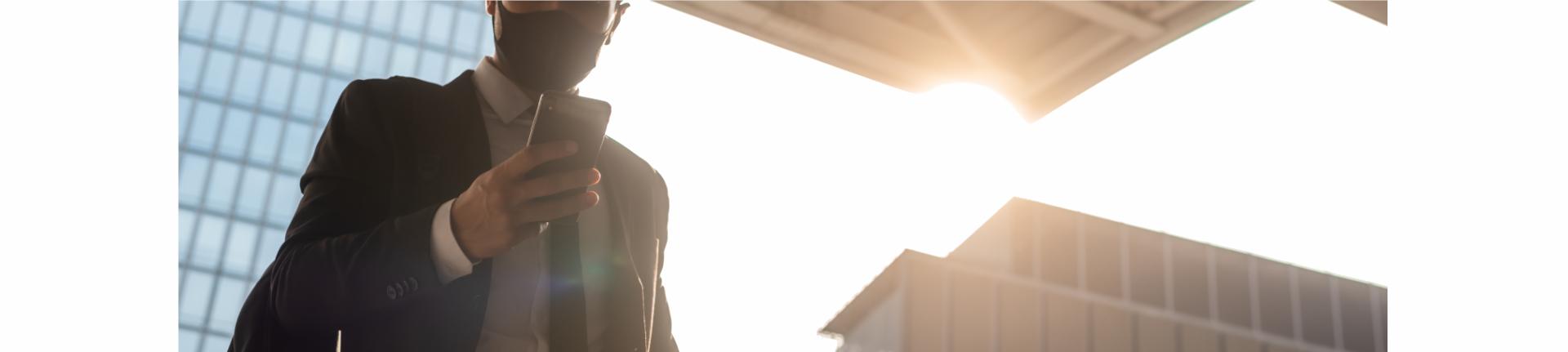 Businessman mit Maske vor Hochhäusern und Sonne Jobsuche im Sommer 2021